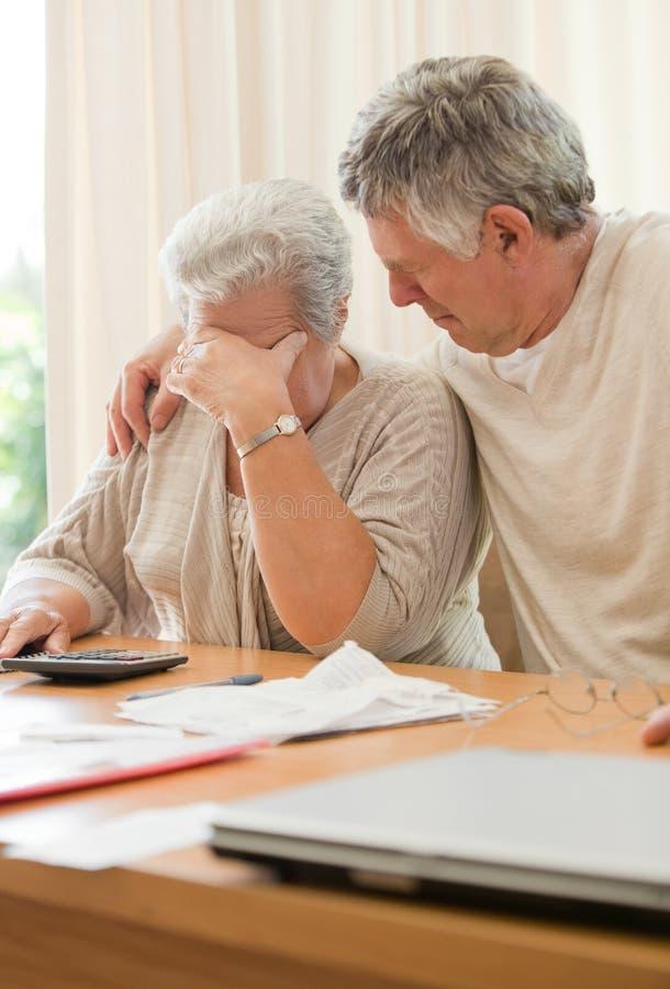 计算他们的国内汇票的哀伤的成熟夫妇 免版税图库摄影