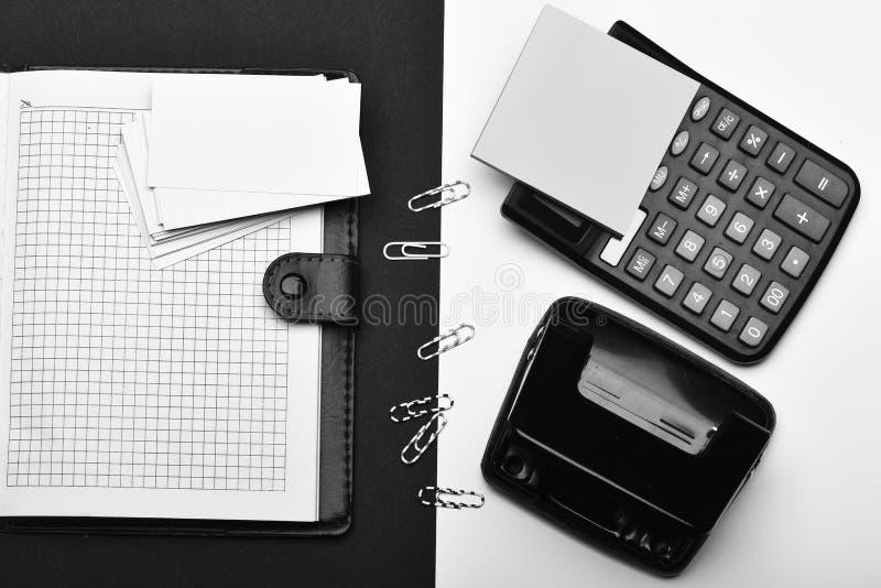 计算器、便条纸、打孔器和纸夹在组织者对面 图库摄影