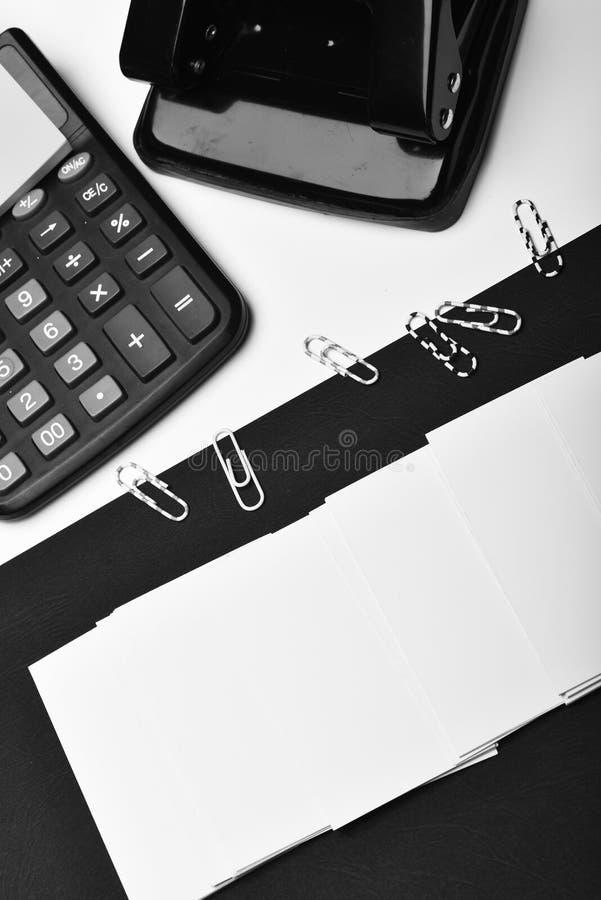 计算器、便条纸、纸夹和打孔器 企业和工作概念:在黑白的文具 免版税库存照片