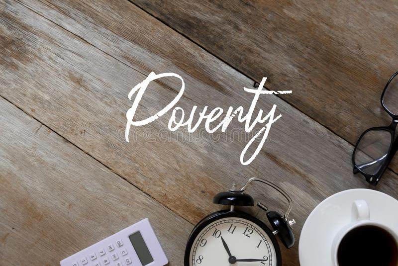 计算器、时钟、一杯在木背景的咖啡和太阳镜顶视图写以贫穷 免版税库存照片