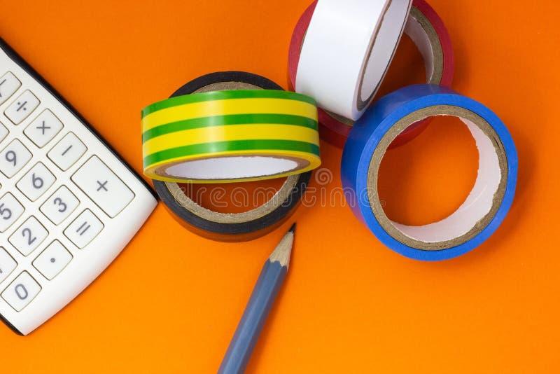 计算器、绝缘胶带和铅笔在橙色背景 免版税库存照片