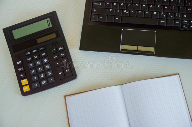 计算器、膝上型计算机和笔记薄在白色桌上 办公室项目 ?? 库存照片