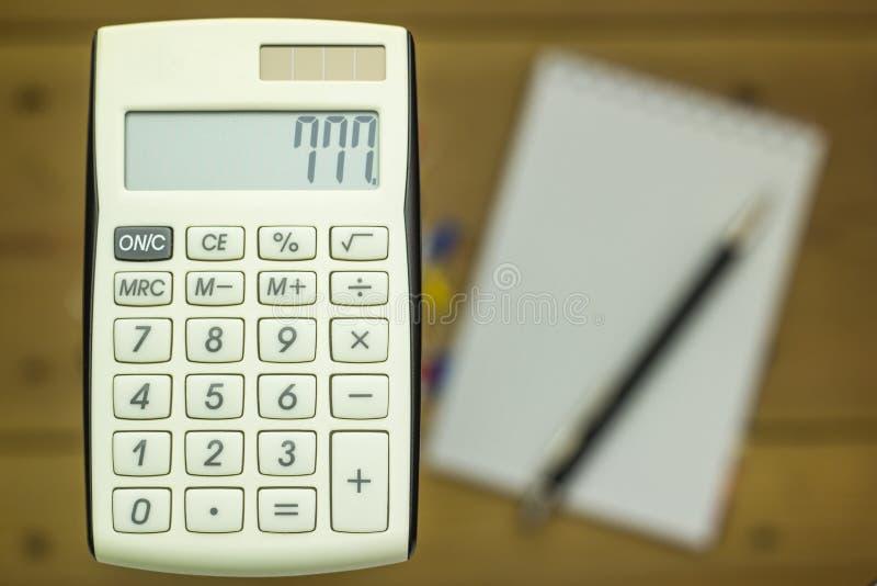 计算器特写镜头在木背景的与笔记本 库存照片