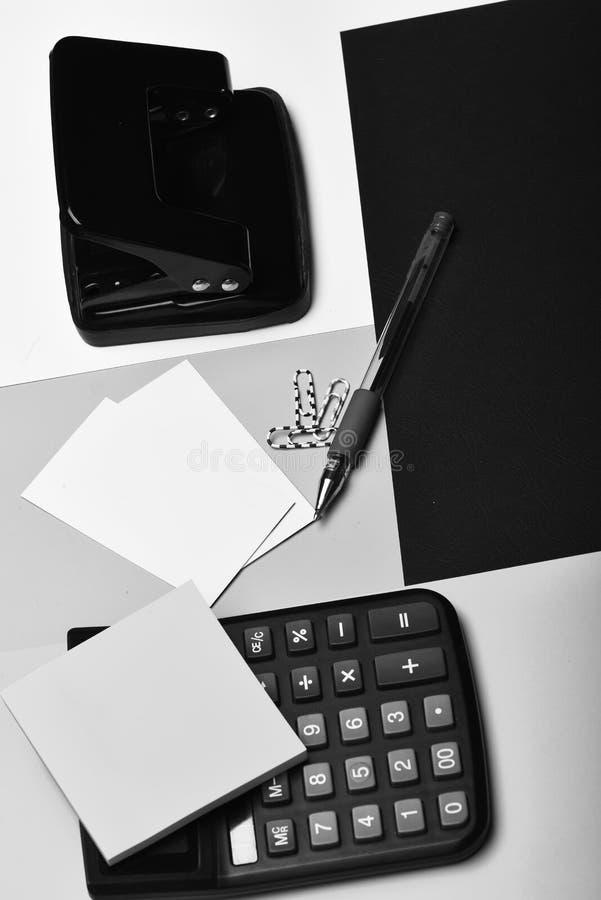 计算器,打孔器,名片,便条纸,纸夹,笔 图库摄影