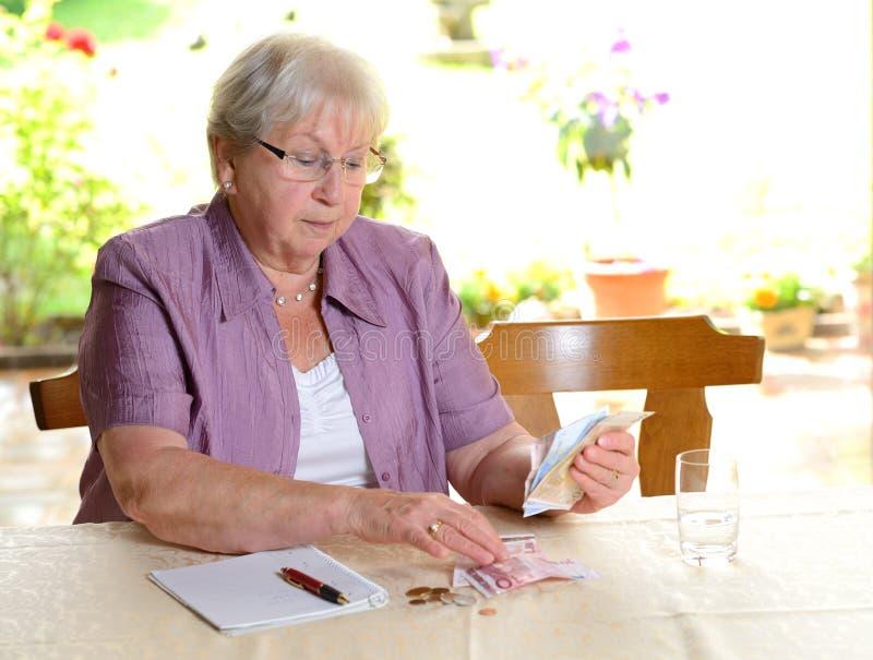 计算她的金钱的女性前辈 免版税库存照片