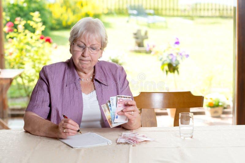 计算她的预算的女性前辈 免版税库存照片