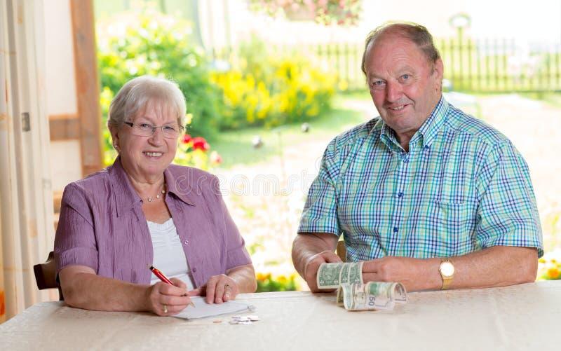 计算她的预算的更旧的夫妇 图库摄影