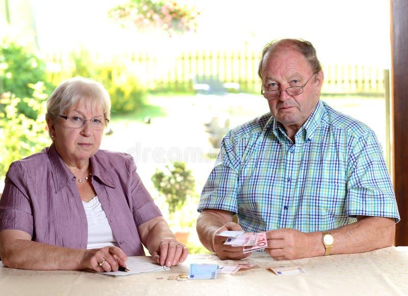 计算她的预算的更旧的夫妇 免版税库存照片