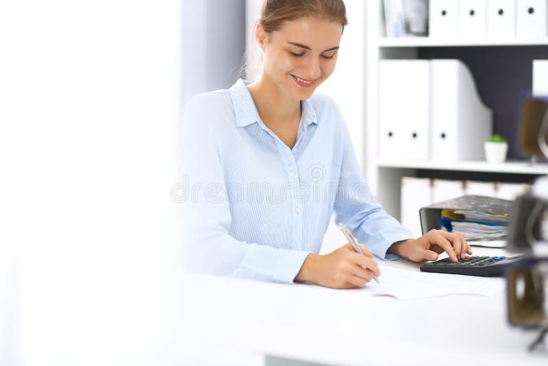计算或检查平衡的妇女簿记员或财政审查员,写报告 国税局在工作 免版税库存图片