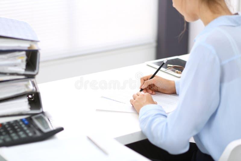 计算或检查平衡的未知的女性簿记员或财政审查员,写报告,特写镜头 内部 免版税库存照片