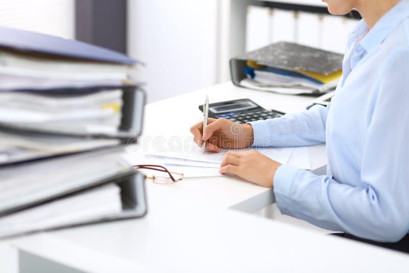 计算或检查平衡的未知的女性簿记员或财政审查员,写报告,特写镜头 内部 库存照片
