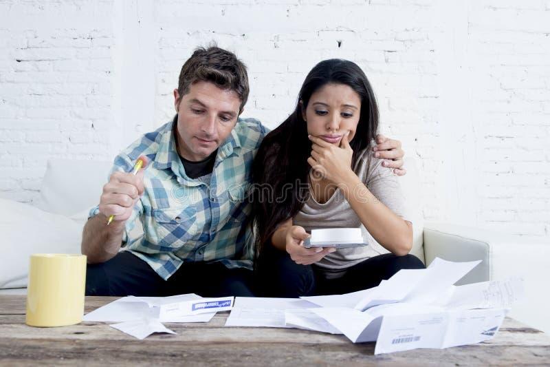 计算月度费用的年轻哀伤的夫妇客厅长沙发在重音在家担心 免版税库存照片