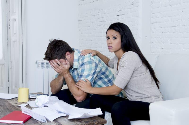 计算月度费用的年轻哀伤的夫妇客厅长沙发在重音在家担心 库存照片