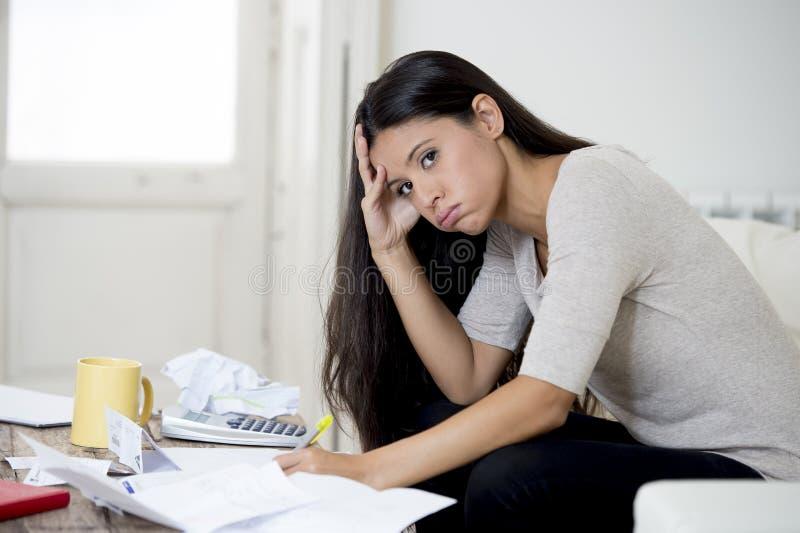 计算月度费用的年轻有吸引力的拉丁妇女客厅长沙发在重音在家担心 免版税库存图片