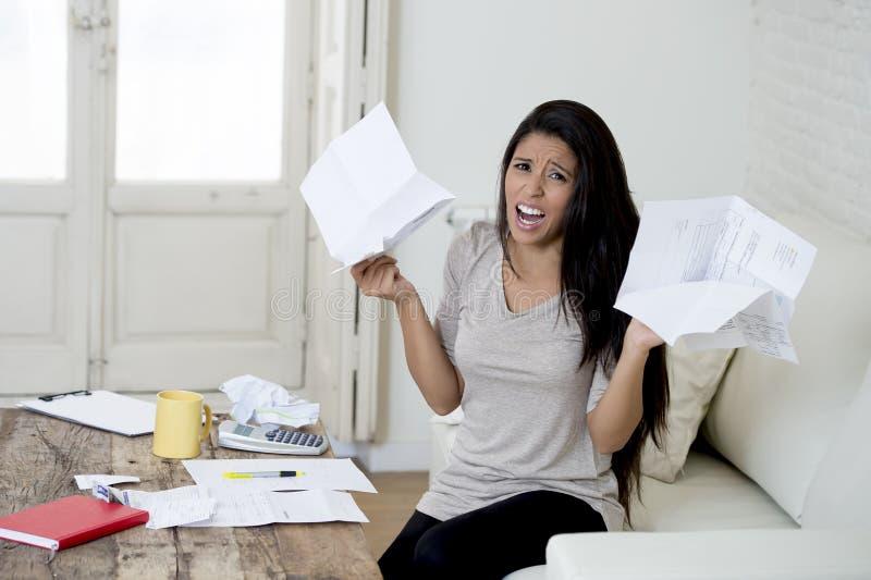 计算月度费用的年轻有吸引力的拉丁妇女客厅长沙发在重音在家担心 免版税库存照片