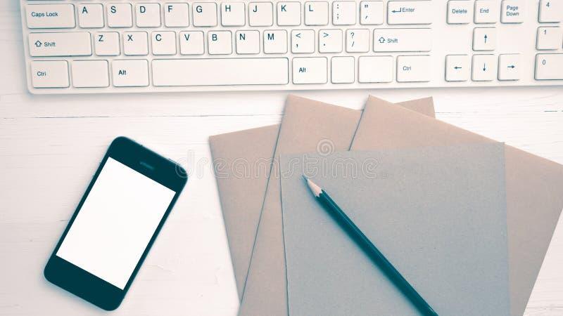 计算机和手机有包装纸和铅笔葡萄酒样式的 免版税库存照片