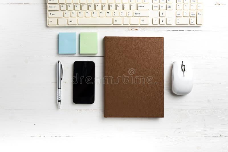 计算机和棕色笔记本有办公用品的 免版税图库摄影