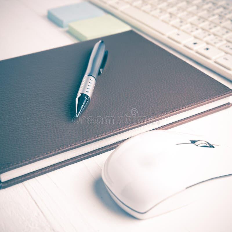 计算机和棕色笔记本有办公用品葡萄酒样式的 免版税库存照片