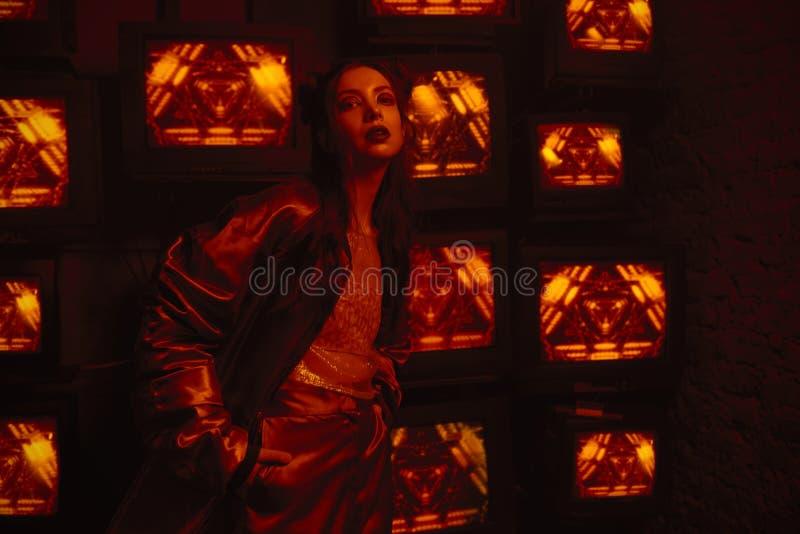 计算机国际庞克与穿当代体育服装的模型的样式射击对电视墙壁  图库摄影