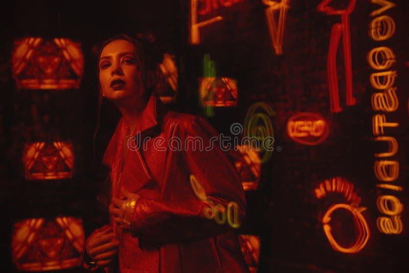 计算机国际庞克与穿红色骑自行车的人夹克的模型的样式射击对电视墙壁  库存图片
