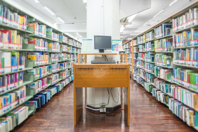 计算机在有许多书和架子的一个图书馆里 免版税库存图片