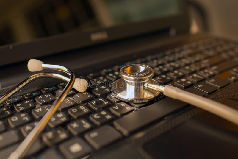 计算机或数据分析-在笔记本键盘的听诊器 免版税库存图片