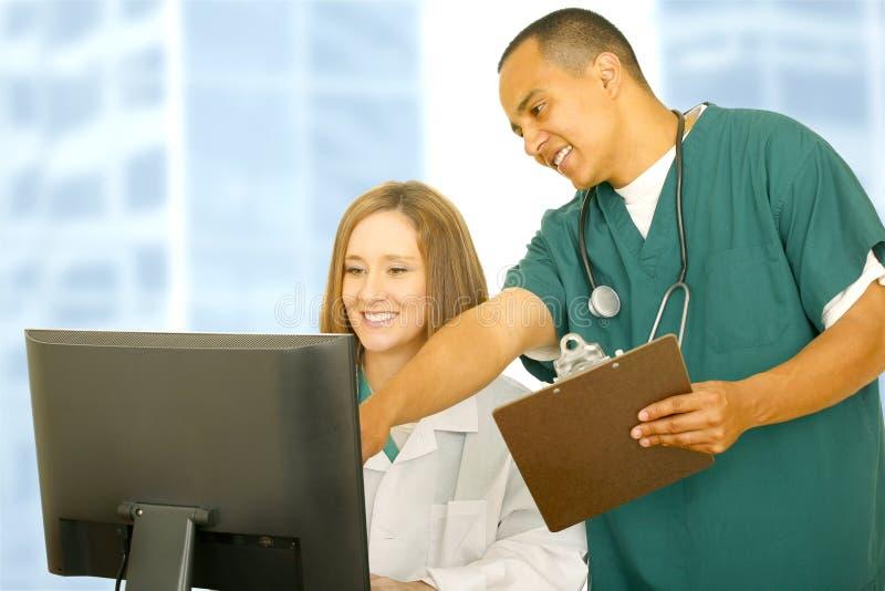 计算机指向屏幕的医生护士 免版税库存图片