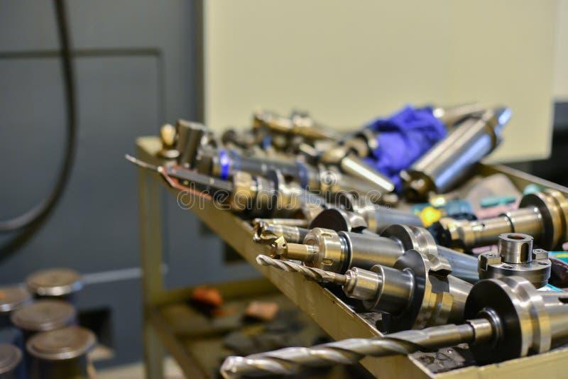 计算机数控机床的设备,钻子,切削刀,在桌上的焊接的谎言在设备附近 免版税库存图片