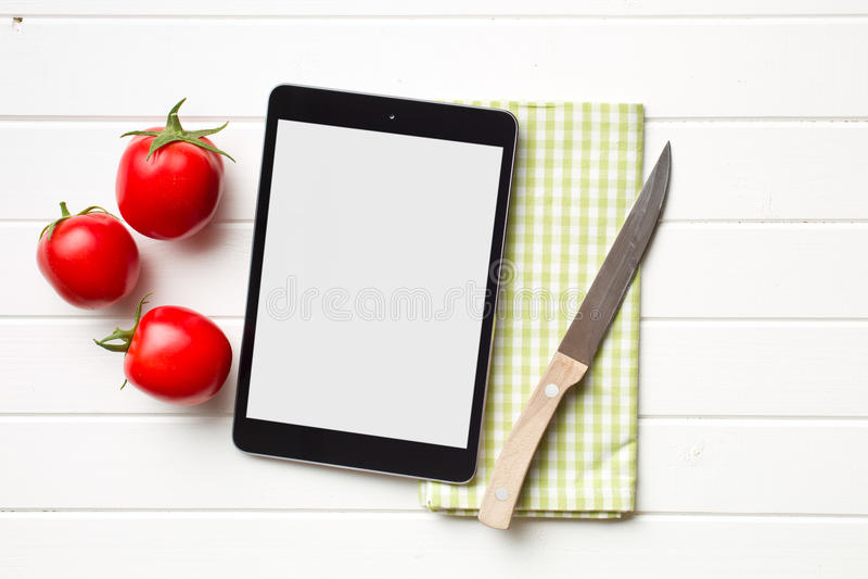 计算机片剂和蕃茄 库存图片