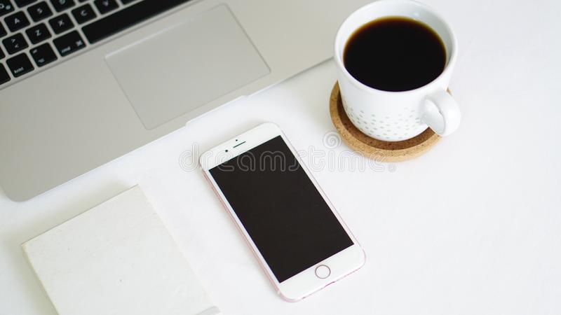 计算机电话和笔记薄在白色背景桌上 免版税库存照片