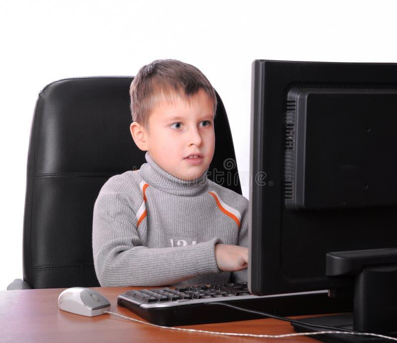 计算机监控程序坐的少年 免版税库存图片