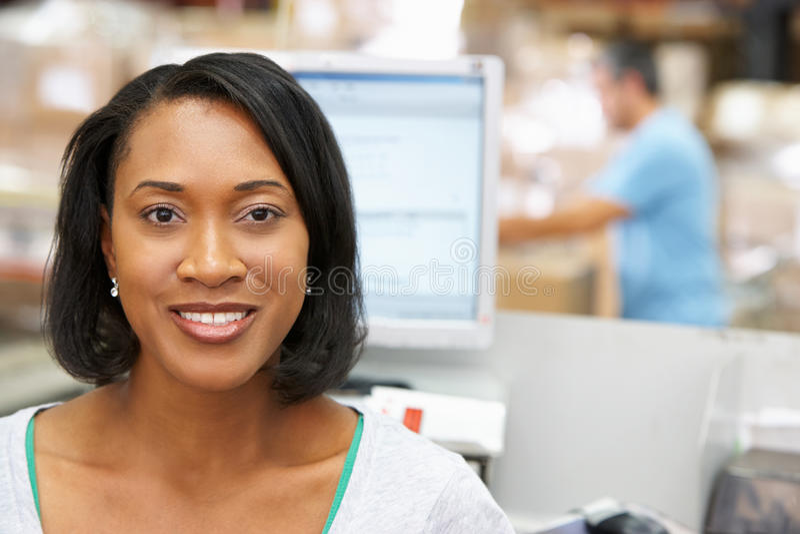 计算机终端的妇女在配给物仓库里 免版税库存图片