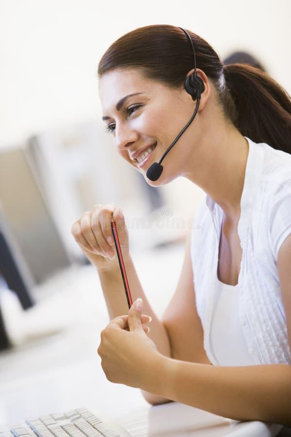 计算机耳机空间微笑的佩带的妇女 免版税库存照片