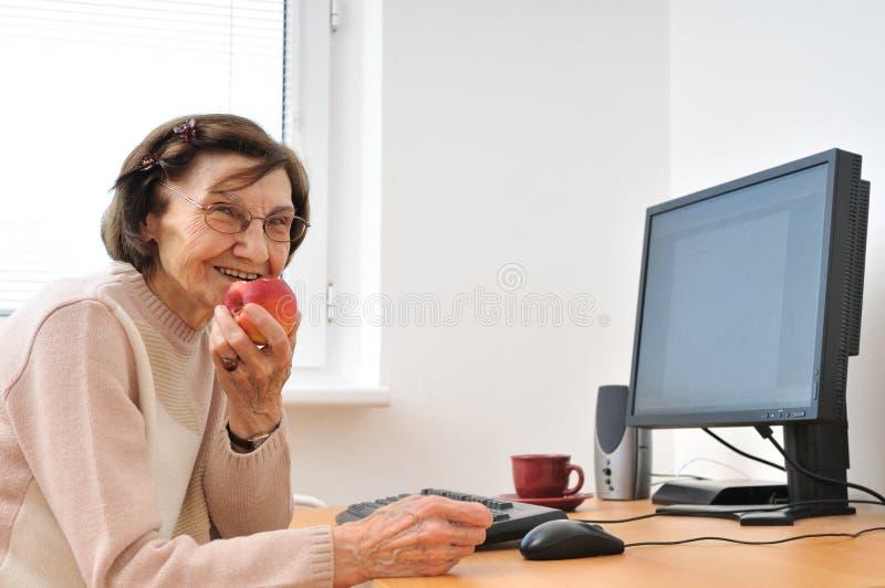 计算机高级微笑的妇女 免版税图库摄影