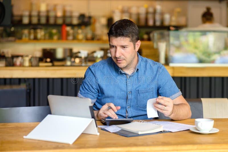 计算活动的金融票据成熟小企业主,使用膝上型计算机和计算器的企业家工作 免版税库存图片