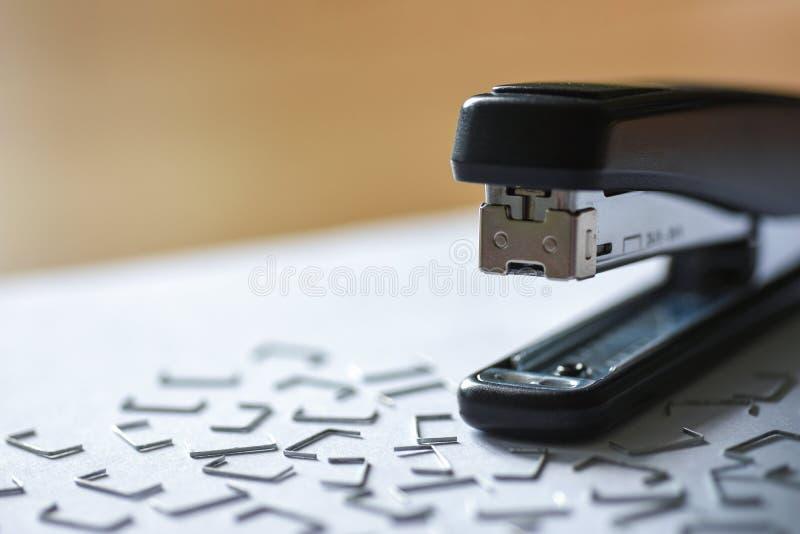 订书机和钉书针在白皮书在办公桌上在办公室 免版税库存照片