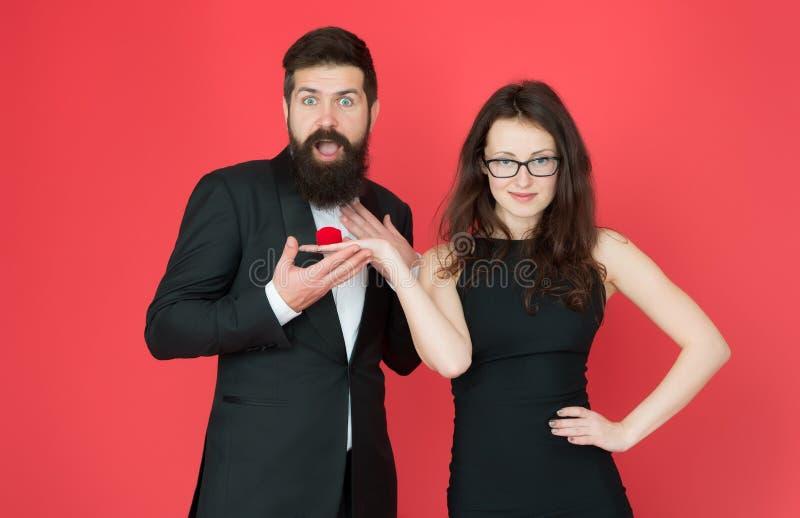 订婚惊奇 妇女提出有胡子的人结婚提议 : 在箱子的圆环 无尾礼服人和典雅的夫人 免版税库存照片