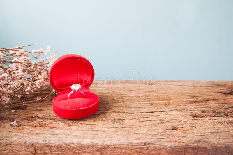 订婚或婚戒,在红色箱子的钻戒在木ta 免版税库存照片