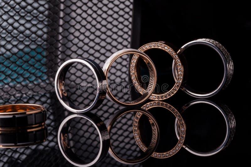 订婚金刚石在黑暗的时尚背景的定婚戒指带与反射,被隔绝,特写镜头 免版税库存图片