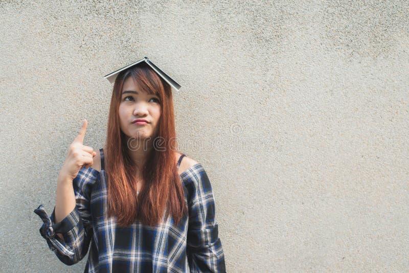 认为与一本书的微笑的年轻美丽的亚裔妇女在头顶上在混凝土墙背景 库存照片