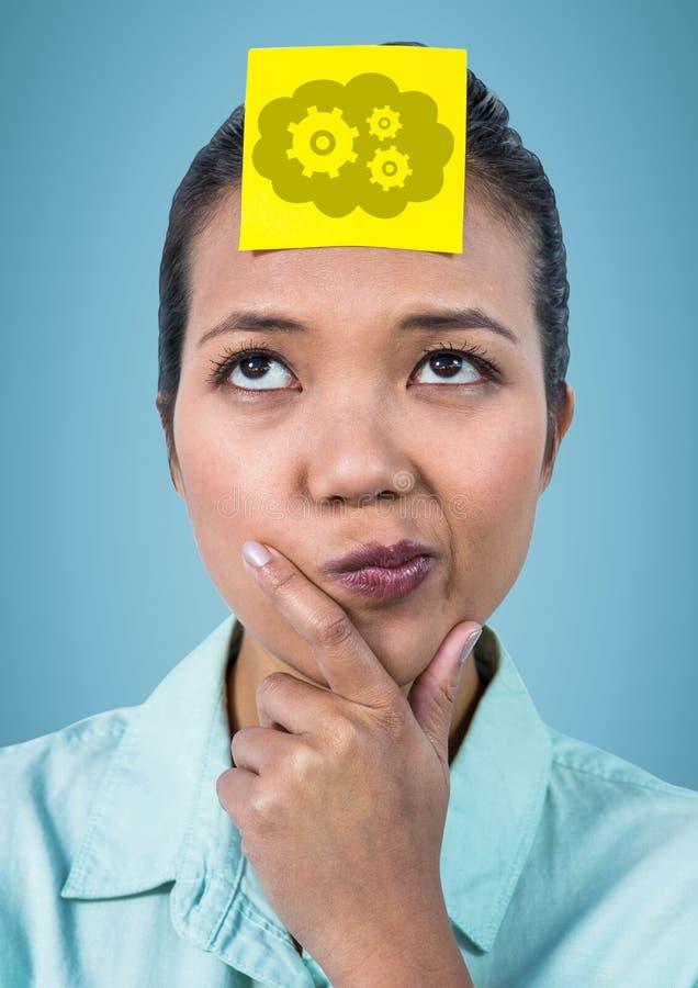 认为与关于顶头显示的云彩和齿轮图表的黄色稠粘的笔记的妇女反对蓝色backgroun 库存照片