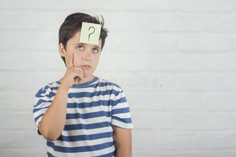 认为与在备忘录岗位的问号的孩子在他的前额 库存照片