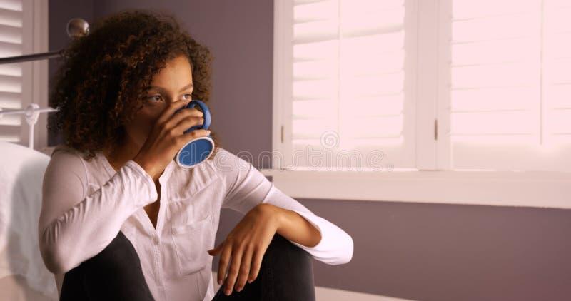 认为和喝从咖啡杯的可爱的年轻黑人妇女 图库摄影