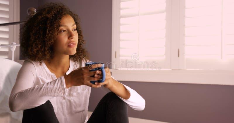 认为和喝从咖啡杯的可爱的年轻黑人妇女 库存照片