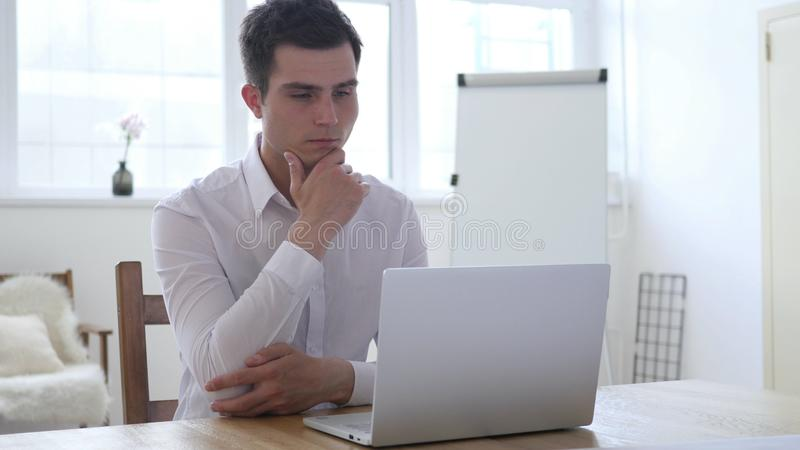 认为和研究膝上型计算机的沉思商人 库存图片