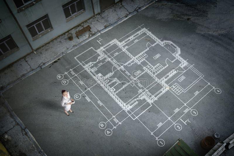 认为在他的计划的妇女工程师 混合画法 免版税图库摄影