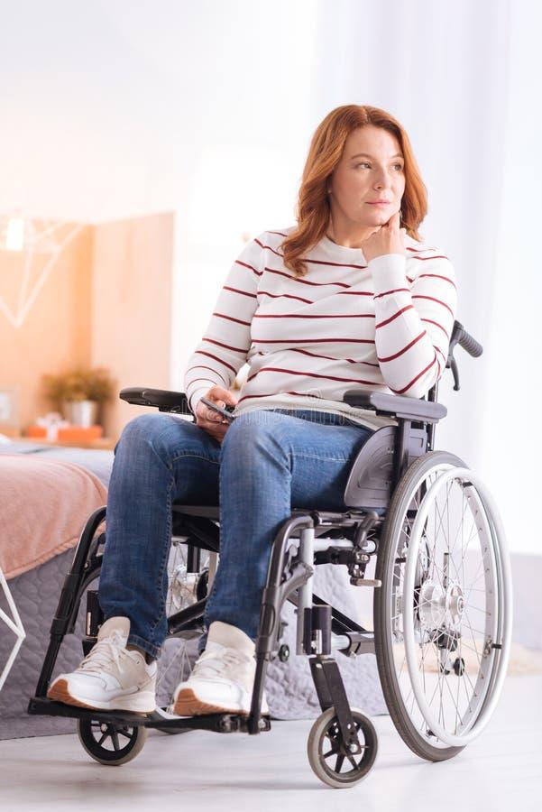 认为在轮椅的严肃的被致残的妇女 库存照片