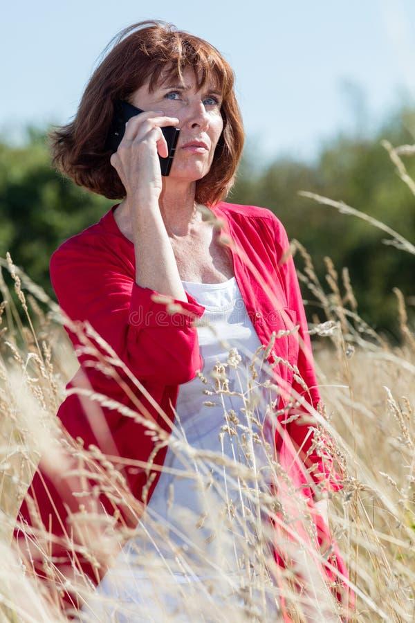 认为在高夏天领域的电话的老化妇女开花 免版税库存照片