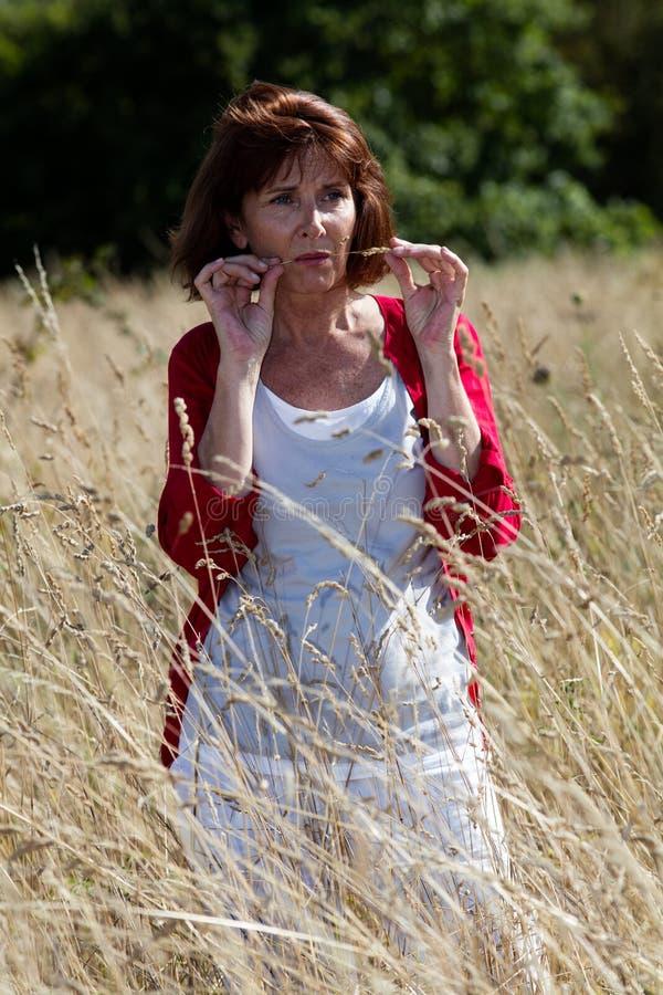 认为在高干燥领域的可爱的中年妇女开花 免版税图库摄影