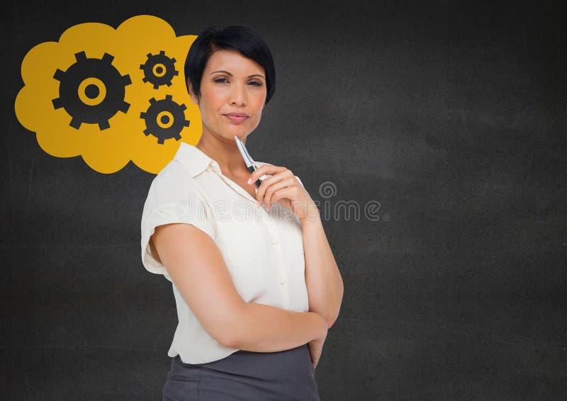 认为对灰色墙壁和黄色云彩的女商人与齿轮图表 免版税库存照片